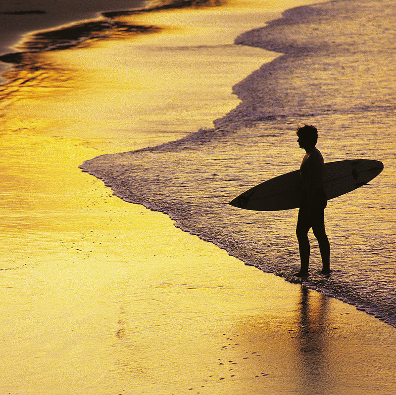 Man standing on the beach in Noosa with his surfboard as the sun sets