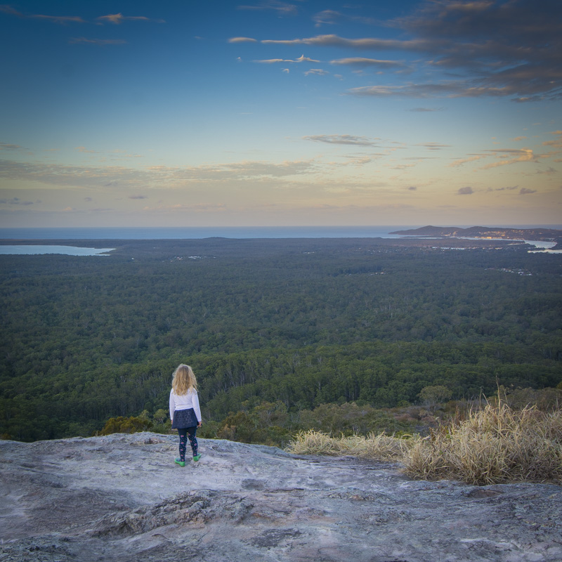 Young girl standing on top of Mount Tinbeerwah looking out over Noosa